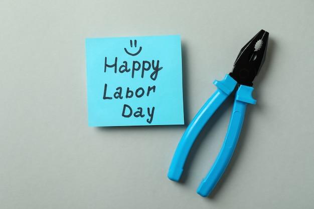 Texto feliz dia do trabalho e alicate em cinza