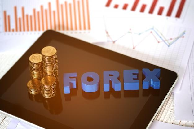 Texto forex e pilha de moedas com tablet e gráfico gráfico financeiro em papel
