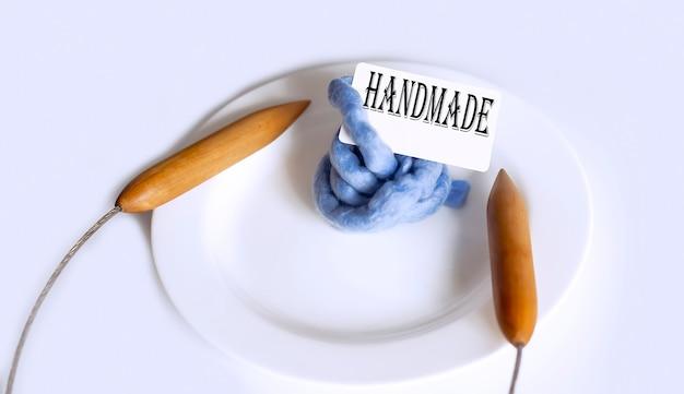 Texto hanmade com grandes agulhas de tricô no prato