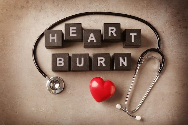 Texto heart burn feito de cubos de madeira e estetoscópio na cor de fundo
