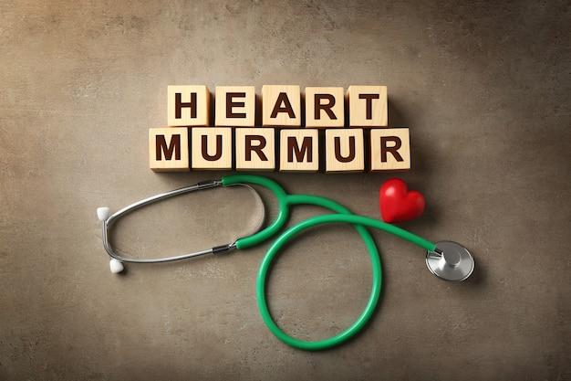 Texto heart murmur feito de cubos de madeira e estetoscópio na cor de fundo