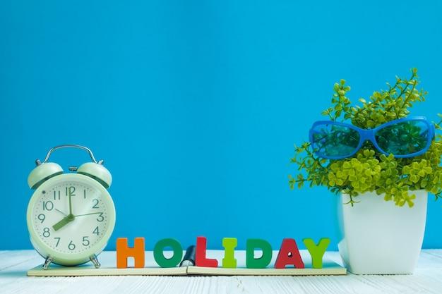 Texto holiday, papel de caderno, despertador e pequena árvore na madeira