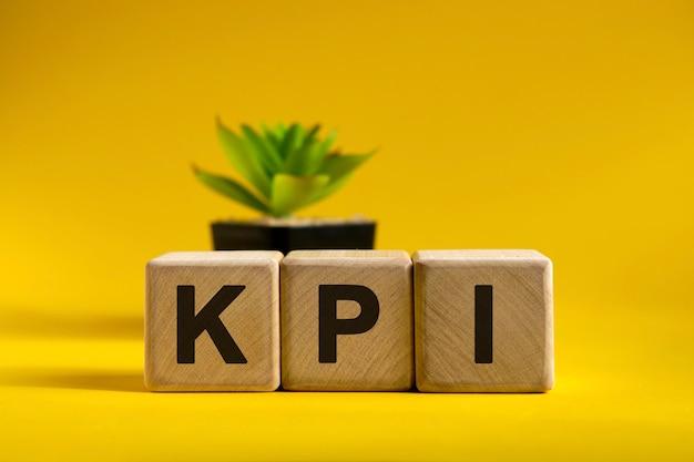 Texto kpi em cubos de madeira em uma superfície brilhante e um vaso com uma flor atrás