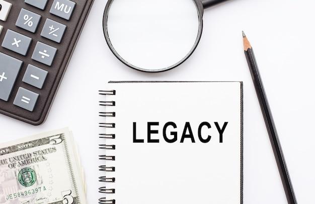 Texto legado, inscrição, frase é escrita em um caderno que está sobre uma mesa branca. conceito de negócios.