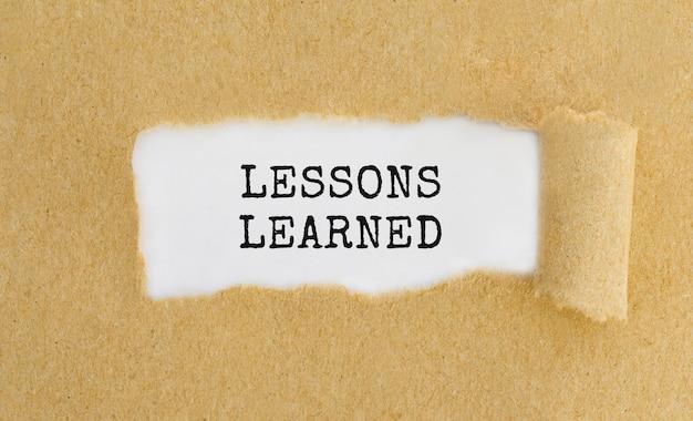 Texto lições aprendidas aparecendo atrás de papel pardo rasgado