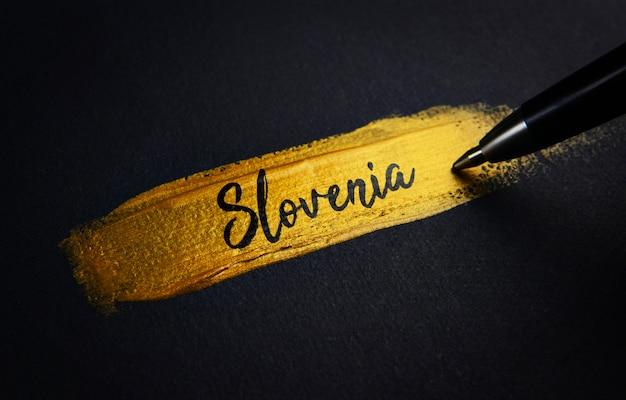 Texto manuscrito de eslovénia no curso de pincel de tinta dourada
