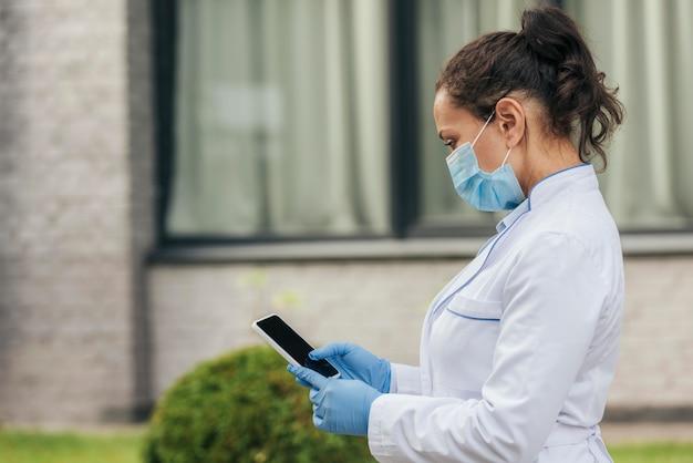 Texto médio de médico enviando mensagens de texto com telefone