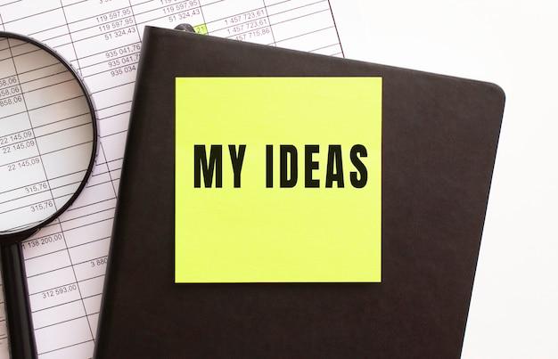 Texto minhas ideias em um adesivo em sua área de trabalho. diário e lupa.