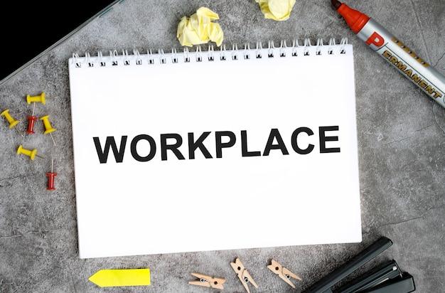 Texto no local de trabalho em um caderno branco com alfinetes, marcador e grampeador em uma mesa de concreto