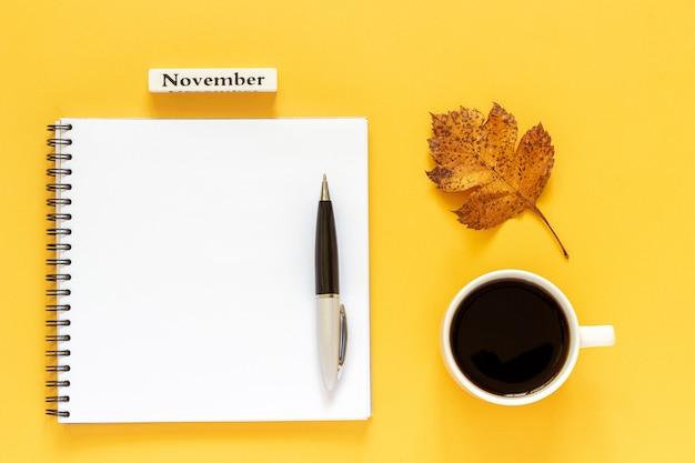 Texto novembro xícara de café, bloco aberto vazio com caneta e folha de outono em fundo amarelo