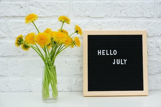 Texto olá julho no quadro de letra preto e buquê de flores amarelas-leão em vaso na parede de tijolo branco de fundo.