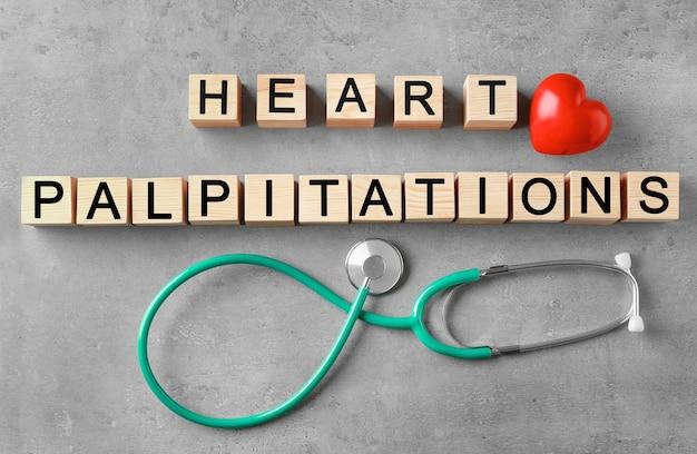 Texto palpitações do coração feitas de cubos de madeira e estetoscópio na cor de fundo