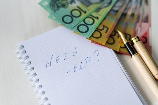 Texto 'preciso de ajuda' no bloco de notas e dólares australianos