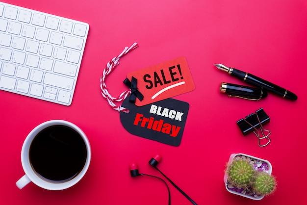 Texto preto da venda de sexta-feira em um tag vermelho e preto com o copo de café no fundo vermelho. compras