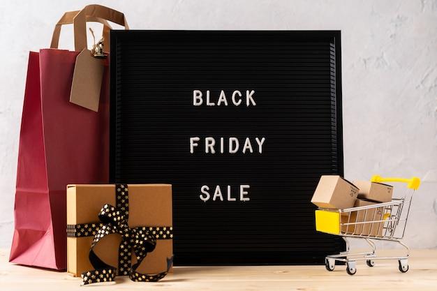 Texto preto sexta-feira no quadro de carta preta, carrinho de compras, bolsa e caixa de presente.