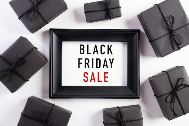 Texto preto venda de sexta-feira na moldura branca com caixa de presente preta