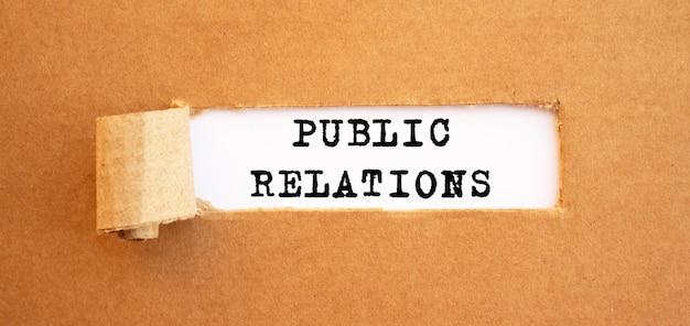 Texto relações públicas aparecendo atrás de papel pardo rasgado