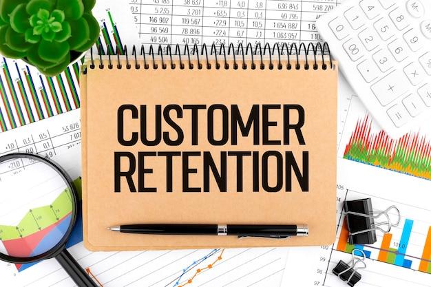 Texto retenção de clientes em notebook, calculadora, lupa, gráficos. conceito de negócio, plana leigos.