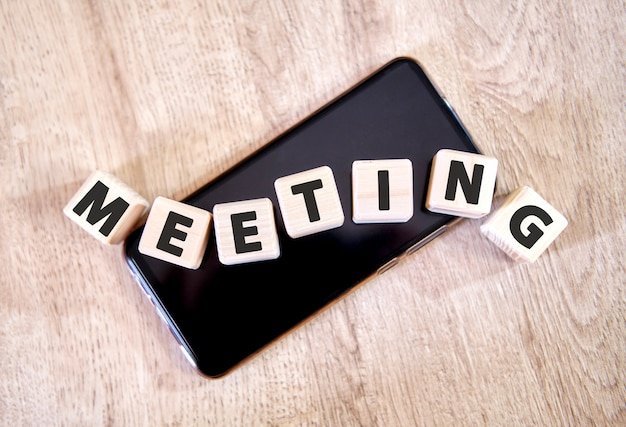 Texto reunião em cubos de madeira em um smartphone preto. cubos colocaram em um smartphone preto na mesa de madeira.