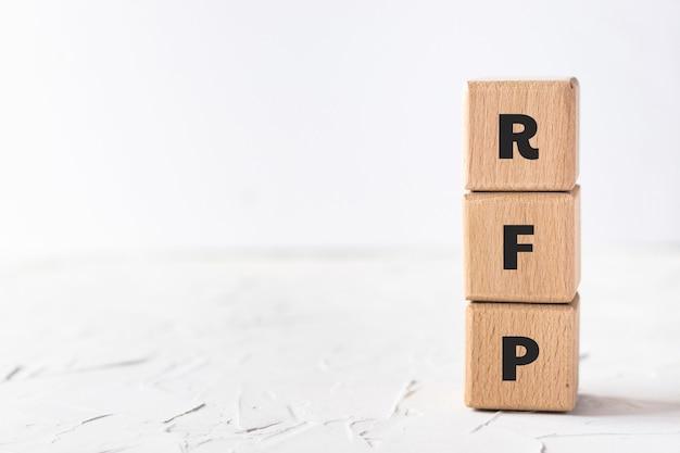 Texto rfp em cubos de madeira em fundo branco texturizado de massa. conceito de negócios e finanças. solicitação de proposta.