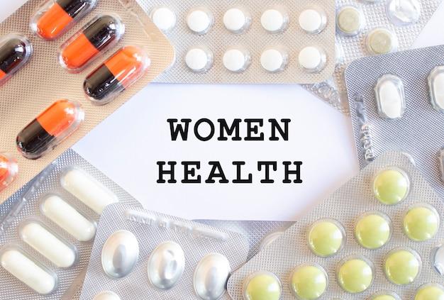 Texto saúde das mulheres em um fundo branco. existem diferentes medicamentos ao redor. conceito médico.