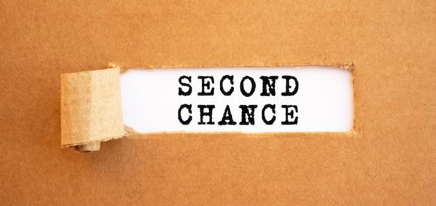 Texto second chance aparecendo atrás de papel pardo rasgado. para o seu design, conceito.