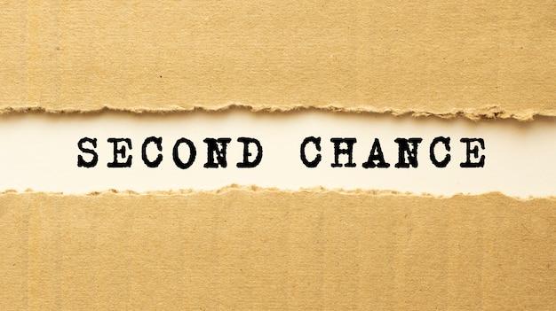 Texto second chance aparecendo atrás de papel pardo rasgado