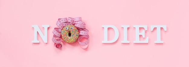 Texto sem dieta e cara engraçada abstrata de mulher de donut com olhos e cabelo da fita de centímetro no prato na parede rosa