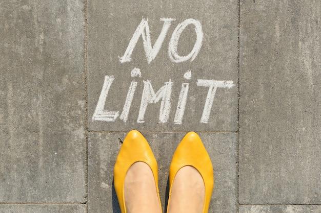 Texto sem limite na calçada cinza com pernas de mulher, vista superior