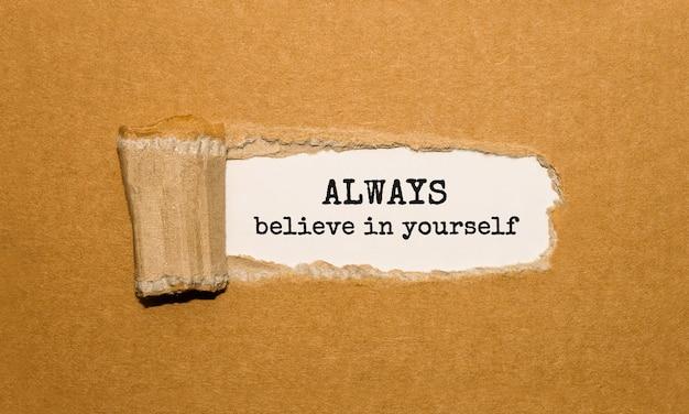 Texto sempre acredite em você aparecendo atrás de um papel pardo rasgado