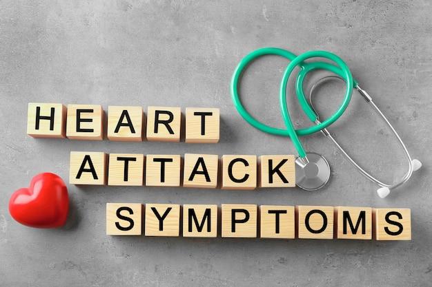 Texto sintomas de ataque do coração feito de cubos de madeira e estetoscópio na cor de fundo