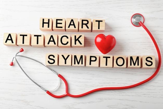 Texto sintomas de ataque do coração feito de cubos e estetoscópio sobre fundo de madeira