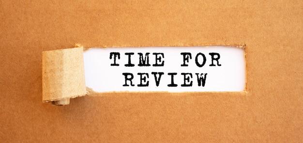 Texto time for review aparecendo atrás do papel marrom rasgado.