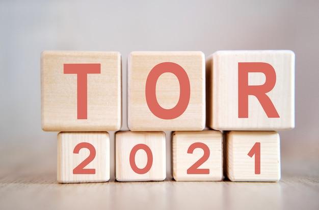 Texto - tor 2021 em cubos de madeira, em superfície de madeira