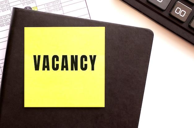 Texto vacancy em um adesivo em sua área de trabalho. diário e calculadora.