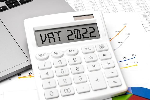 Texto vat 2022 - imposto sobre valor agregado na calculadora, laptop, chatrs, gráficos. plano de negócios deitado.