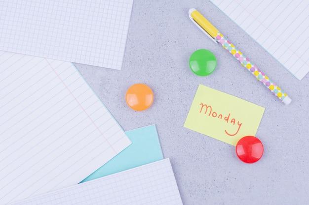 Textos relacionados à volta às aulas em adesivos com alfinetes coloridos e papéis ao redor
