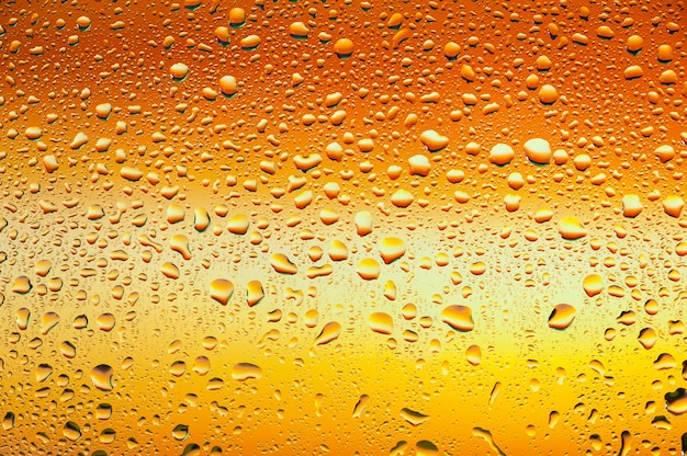 Textura abstrata. gotas de água no vidro com fundo laranja