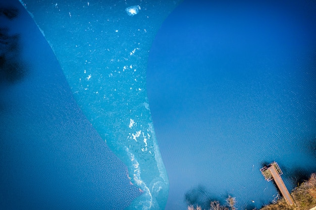 Textura aérea de água e gelo da vista aérea. uma pequena plataforma de metal na margem de um fundo de lago outono