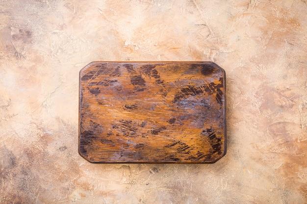 Textura alaranjada, arenosa do fundo da pedra de pedra com placa de corte de madeira velha. vista do topo.