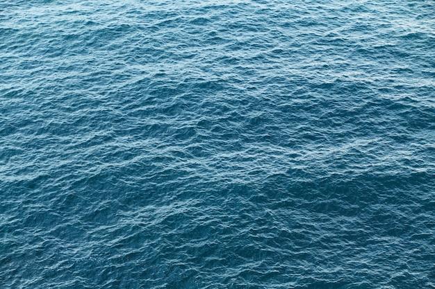 Textura azul da água calma do mar. ondas de luz