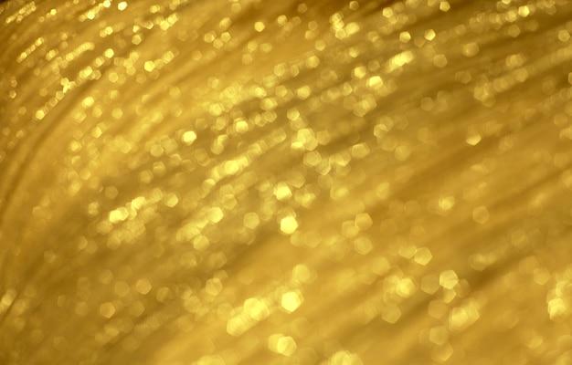 Textura borrada festiva dourada brilhante do tecido.