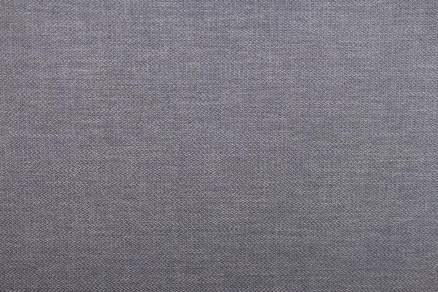 Textura cinzenta detalhada da tela do marrom de matéria têxtil, fundo.