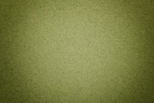 Textura da luz do vintage - fundo do papel verde com vinheta matte. estrutura de papelão kraft de azeitona com moldura.