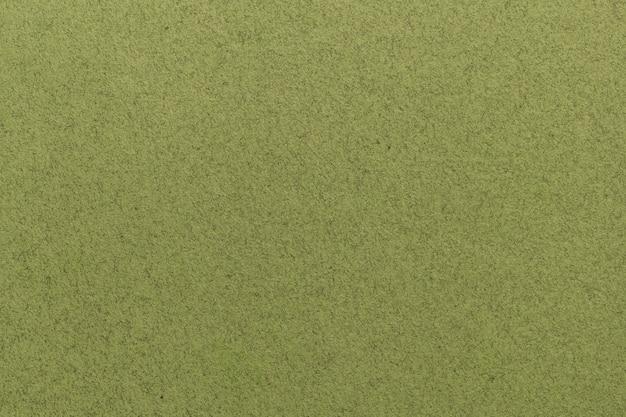 Textura da luz velha - close up do papel verde. estrutura de um papel de parede de papelão denso fosco. fundo de feltro de azeitona