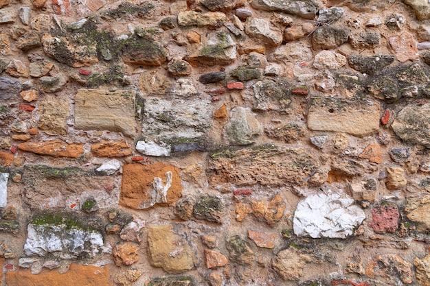 Textura da parede de alvenaria antiga. textura de uma parede de pedra. (tijolos multicoloridos)