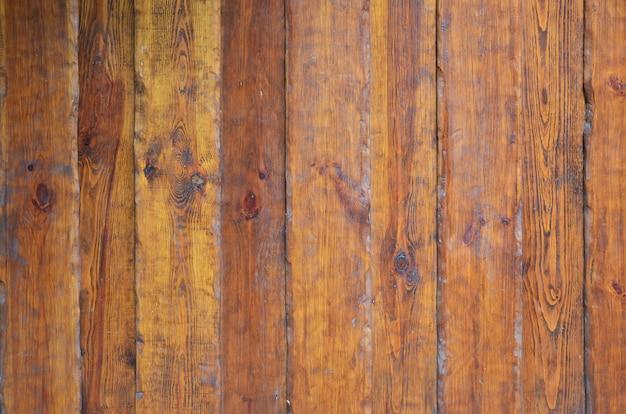 Textura da parede de madeira velha de um número de tábuas riscadas que são envernizadas