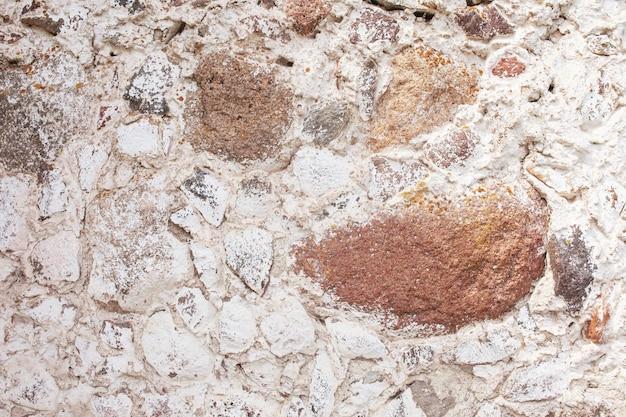 Textura da parede de pedra. fundo decorativo da parede das rochas do mosaico. parede de alvenaria de pedras velhas. revestimento decorativo das paredes externas da casa.