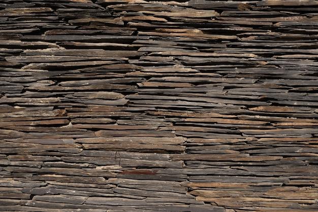 Textura da parede de pedra, muitas pequenas pedras ficam em cima umas das outras, a parede consiste delas