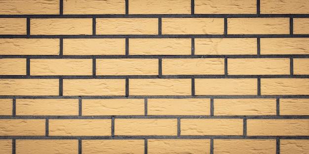 Textura da parede de tijolo, fundo de pedra. padrão de tijolos amarelos. panorama amplo, faixa panorâmica. fachada da arquitetura, superfície lado a lado, quadro de pedra.